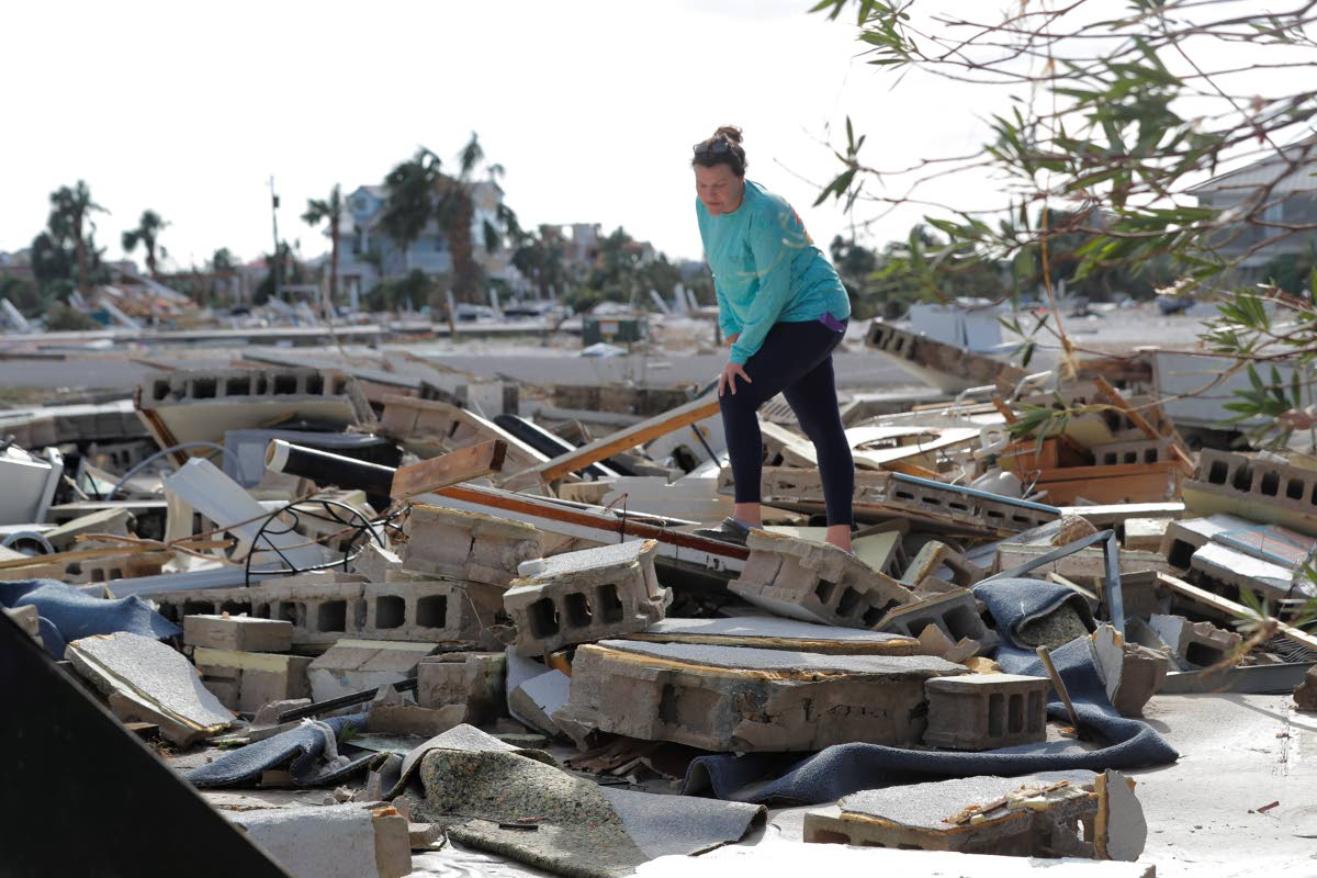 In this October 11, 2018 file photo, Mishelle McPherson looks for her friend Agnes Vicari in the rubble of her home in Mexico Beach, Florida. Vicari stayed in her home during Hurricane Michael and had not been found. The storm that ravaged the Panhandle left incredible destruction. AP Photo