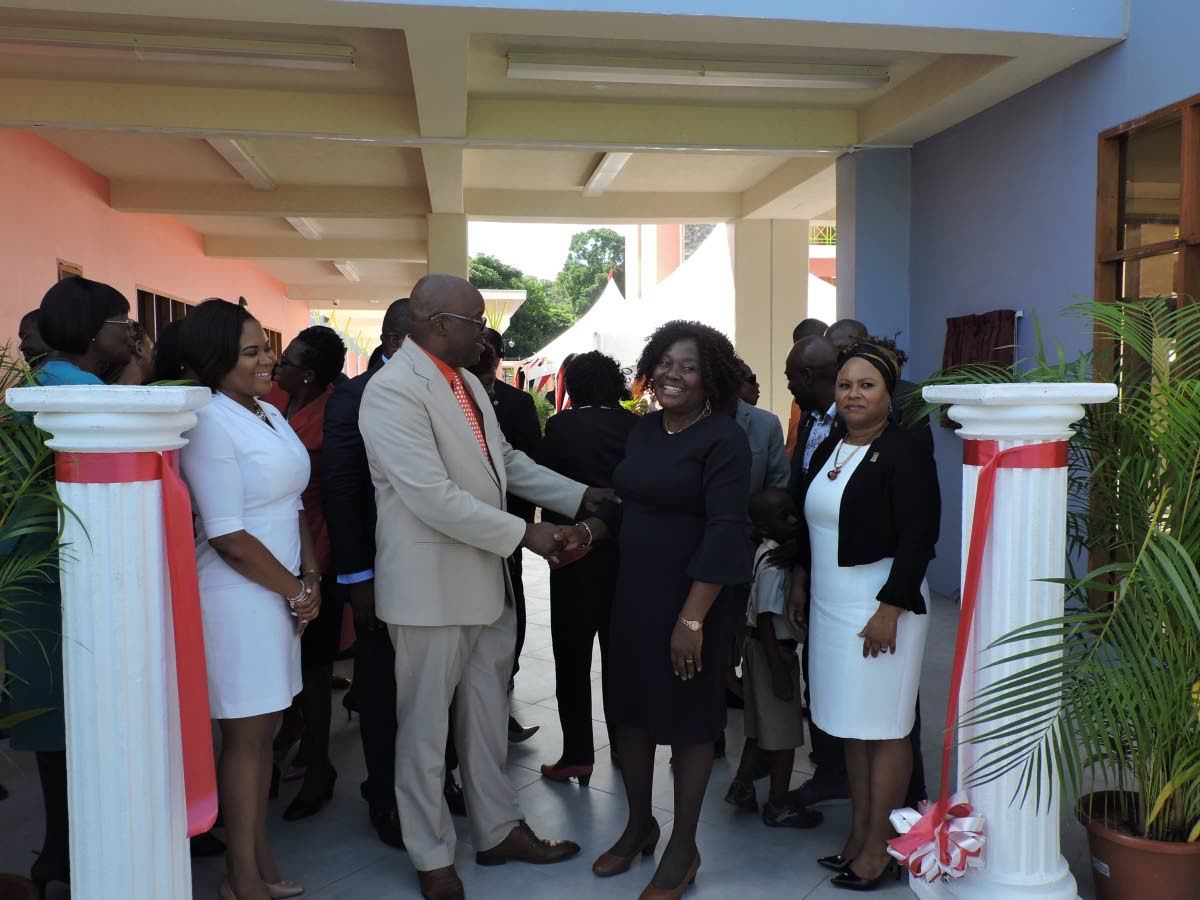THA Chief Secretary and Secretary of Education Kelvin Charles greets acting Principal Patricia Wafe during the commissioning of the Scarborough Roman Catholic School at Smithfield Road on August 29. At left is Sports Minister and MP for Tobago West Shamfa Cudjoe, while THA's Presiding Officer Denise Tsoiafatt Angus looks on at right.