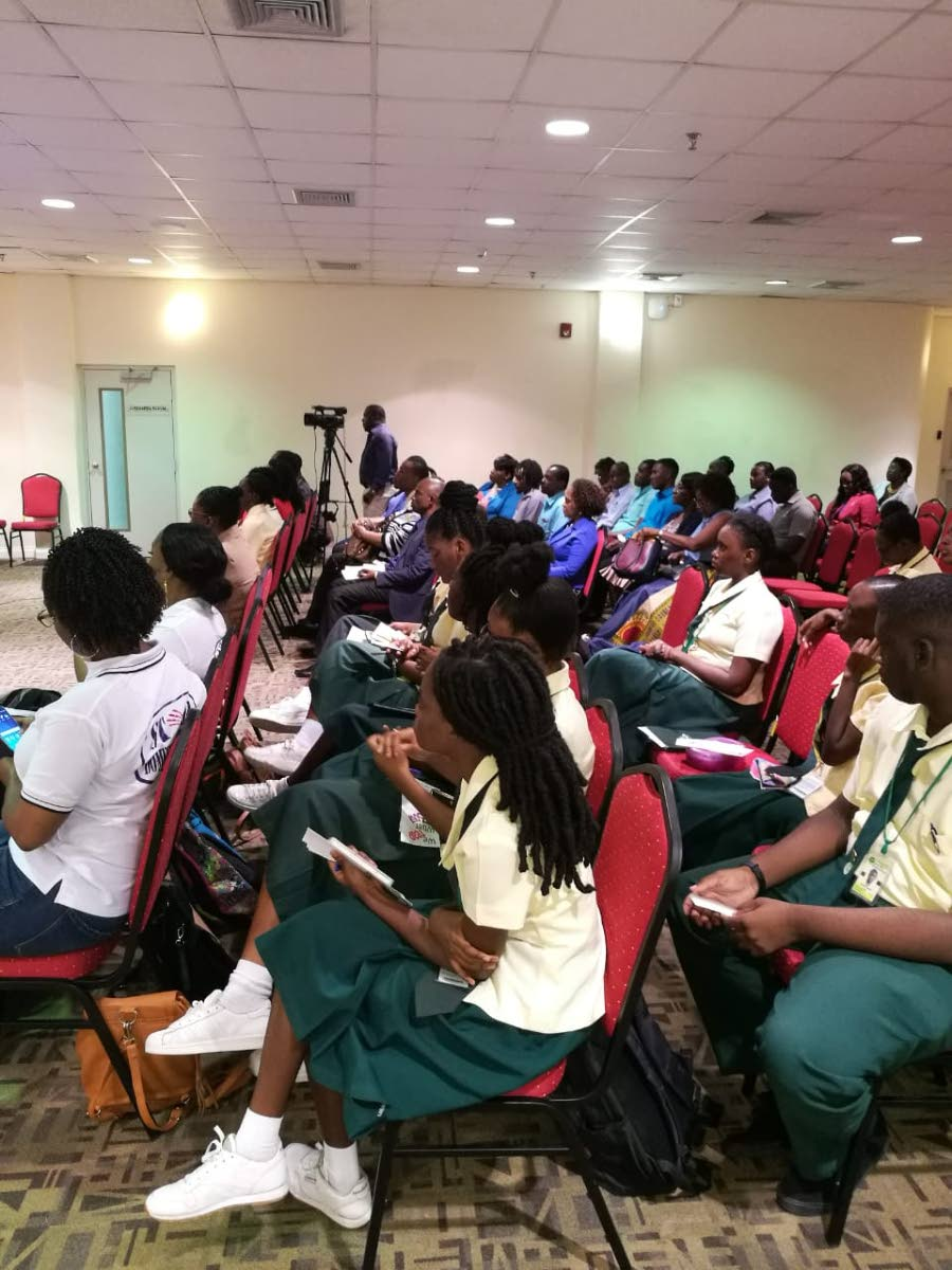 Students of the Signal Hill Secondary school listen to a  presentation by domestic abuse survivor Stacy-Ann Beckles at a symposium,
