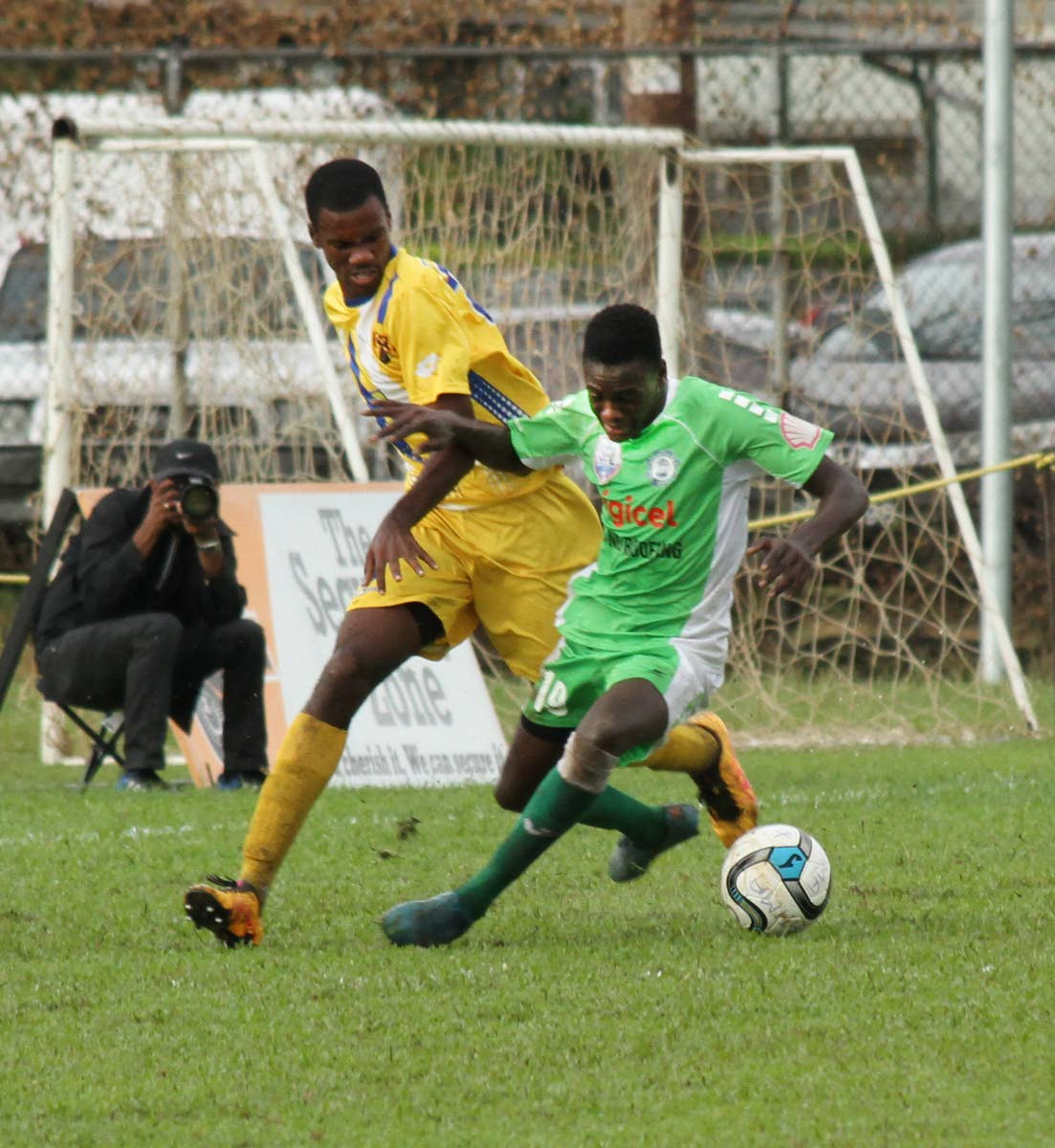 Carapichaima East Secondary's Dexter Neils,right, is challenge by Fatima's Saeed Pompy Charles for the ball as the two teams met yesterday, at Fatima Grounds,Mucurapo.