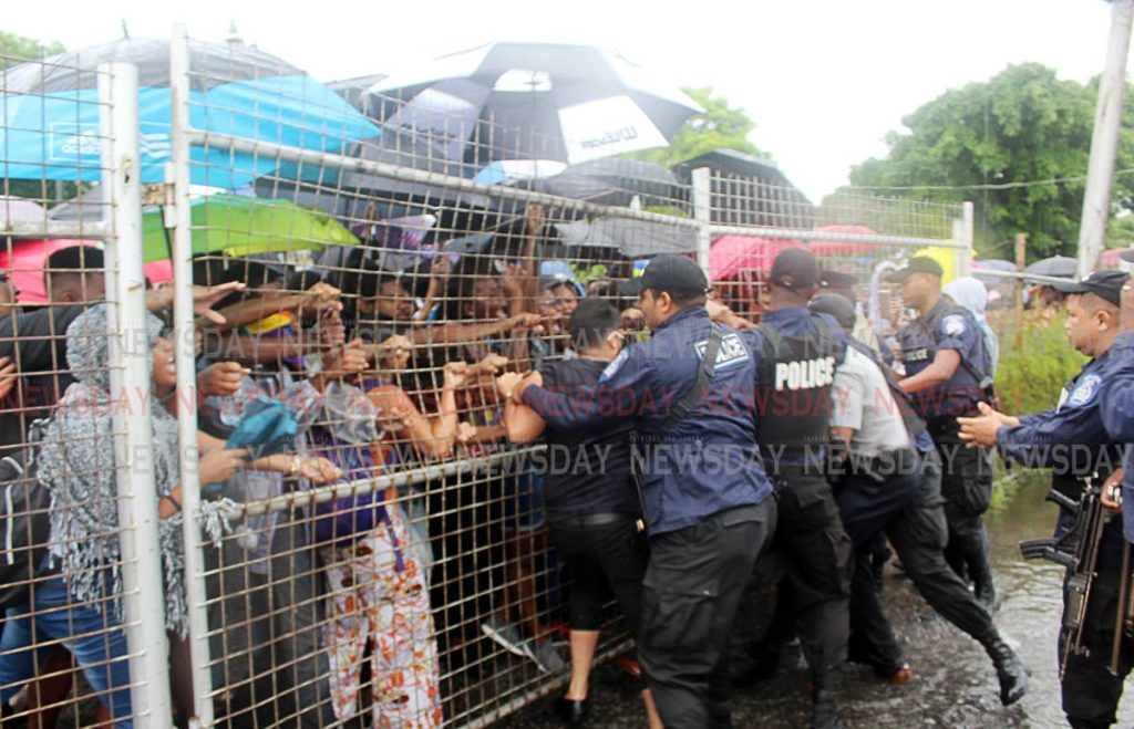 File photo: Police push against the UWI south gate as students push back in an attempt to keep the gate closed in October.