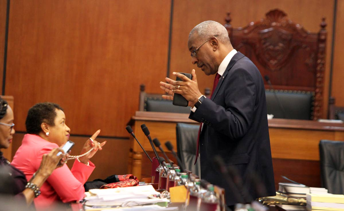 Minister in the Ministry of Finance Allyson West speaks with Public Utilities Minister Robert Le Hunte during a break in yesterday's Senate debate on the budget.