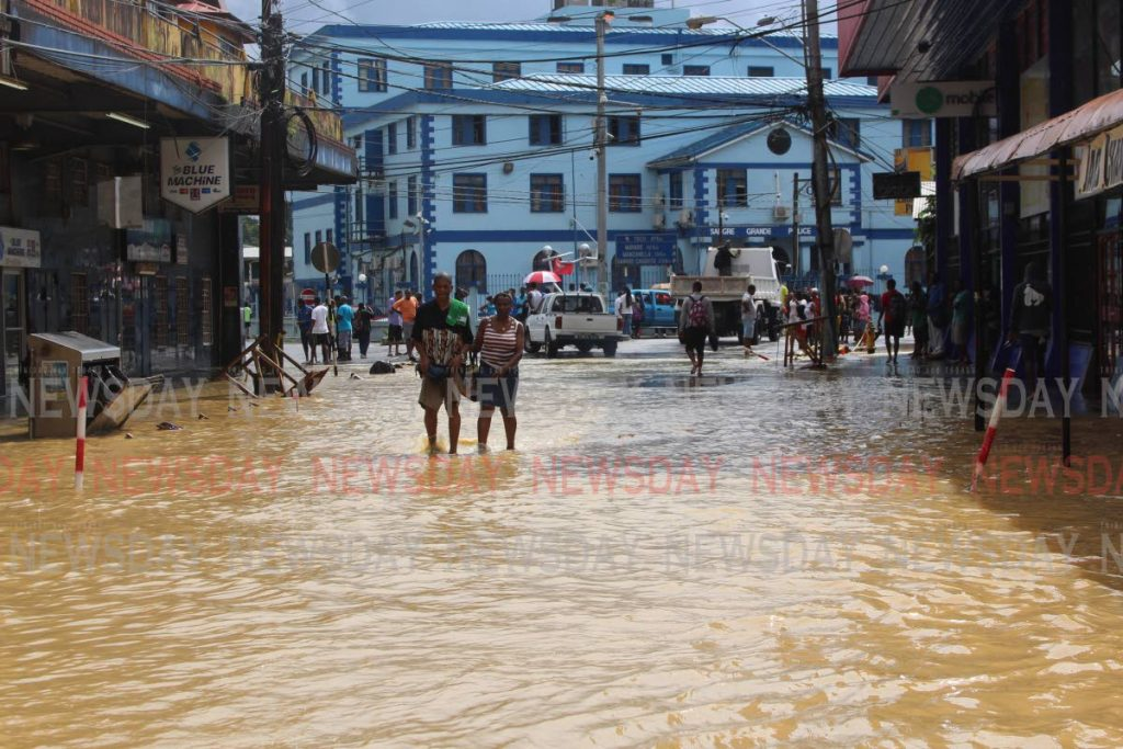 File photo: People walk along the flooded Eastern Main Road leading to the police station in Sangre Grande.   PHOTO BY ENRIQUE ASSOON