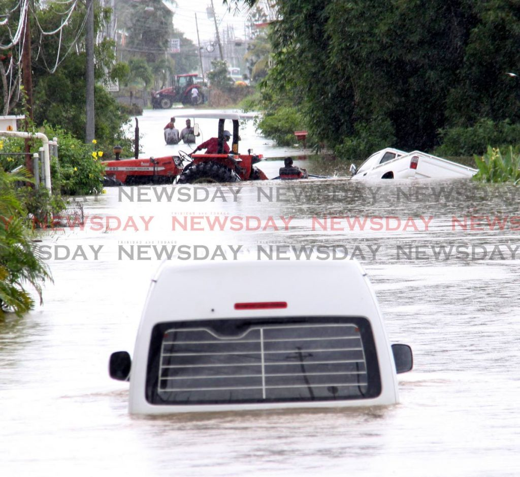 A tractor aids in retrieving a van just off the Sir Solomon Hochoy Highway in the vicinity of Caroni. The vehicle in the forefront stalled while attempting to cross the flood waters. In the background, another tractor lends assistance. PHOTO BY ANGELO MARCELLE.