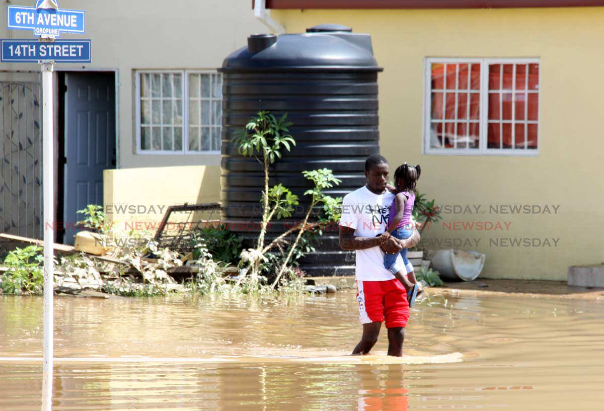A man carries a child through floodwaters in Oropoune Gardens, Piarco on October 20. PHOTO BY ANGELO MARCELLE