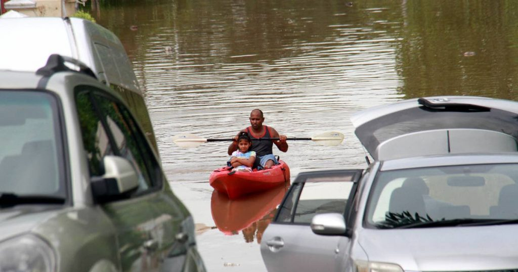 A man sails in a kayak with a child through floodwaters in Mayaro yesterday. PHOTO BY ANIL RAMPERSAD