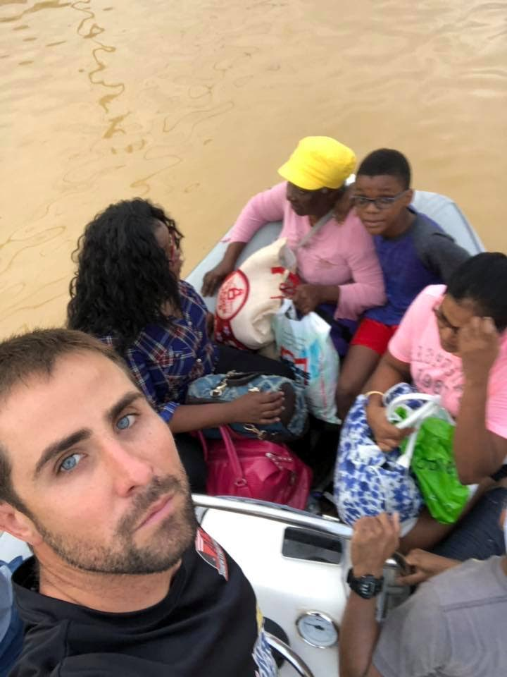 TT sailor Andrew Lewis, left, helping people affected by floods, on Saturday.