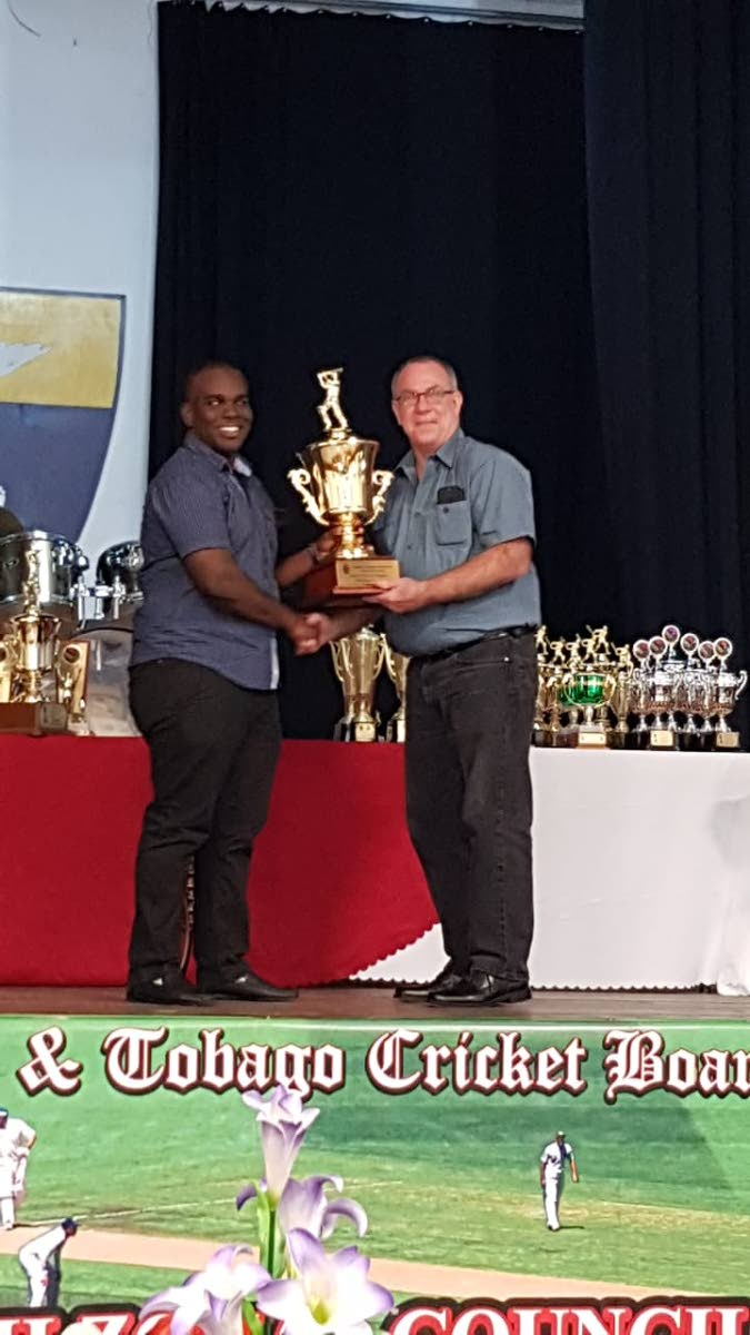Miabah Uthman of Police, left, collects the 2017 Cricketer of the Year award on behalf of Dane Teelucksingh, from vice-chairman of the North Zonal Council Andrew Hirst.