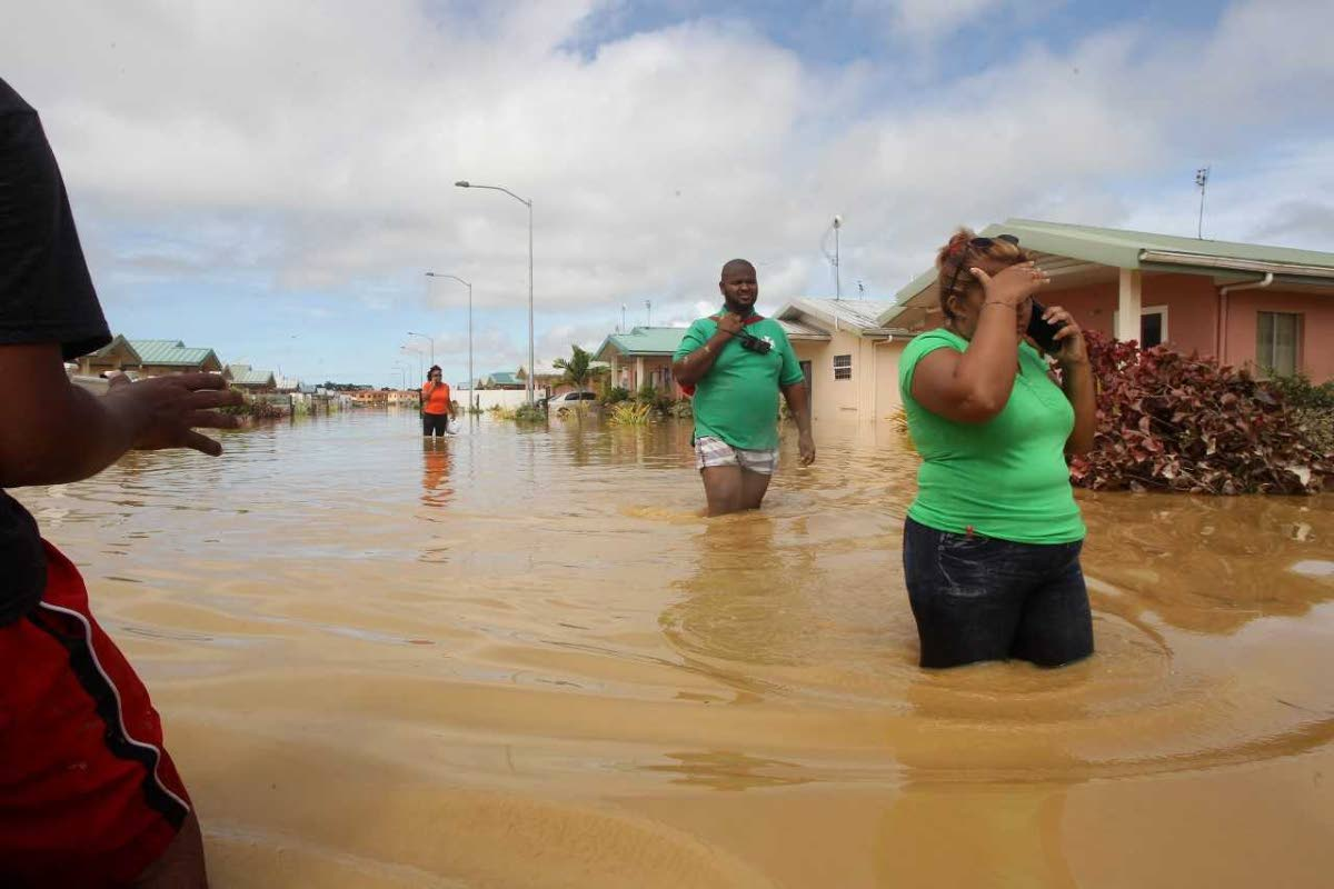 Flood victims wade through waters at Greenvale.