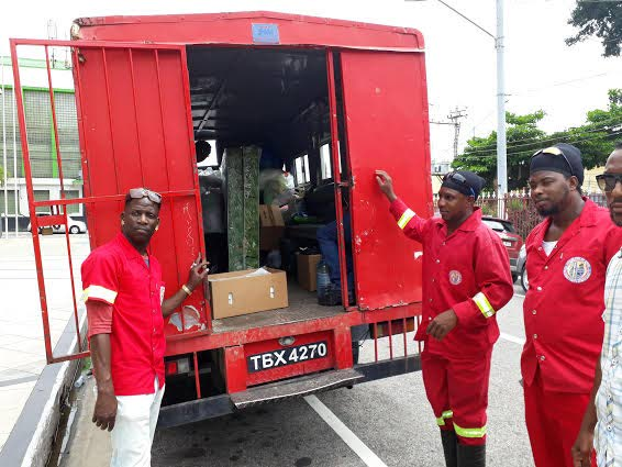 Workers of the Port of Spain City Corporation load relief items including mattresses and foodstuff on a truck en route to the Greenvale community of La Horquetta yesterday.