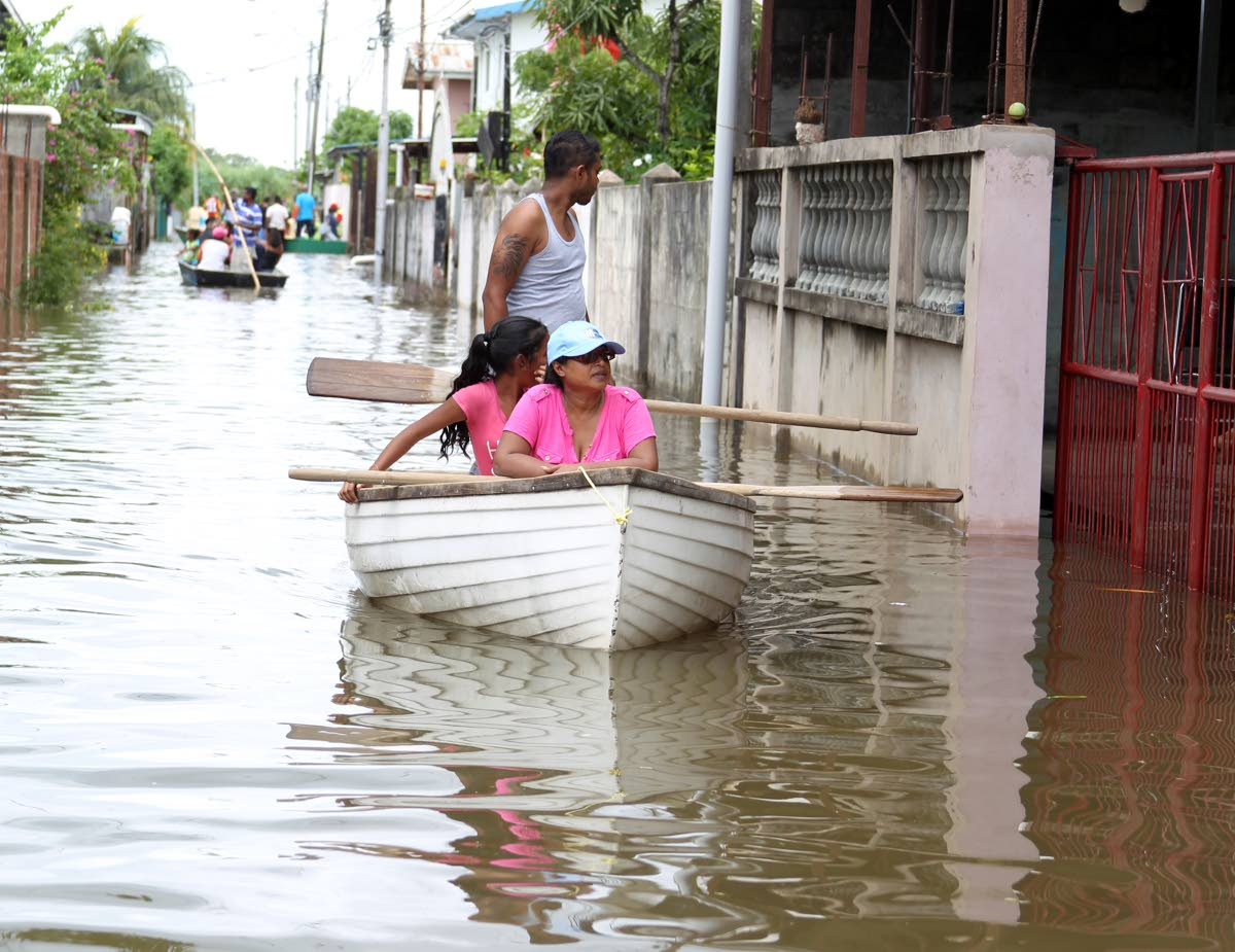 Surveying the damage, residents who mobilised themselves with boats and relief items come to the aid of their neighbours of the El Socorro South community on October 23.
