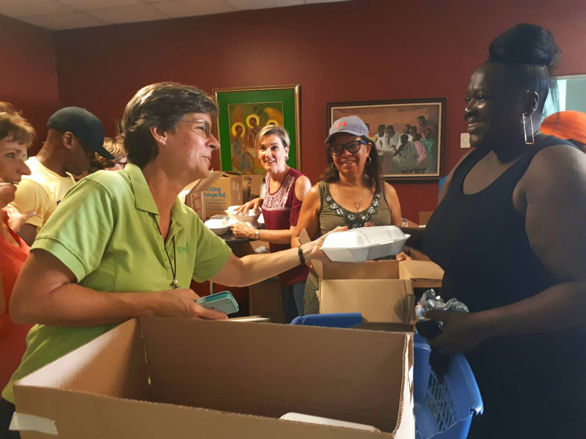 Assistant director of Living Water Community Rosemarie Scott and Sharon Sandy happily package food for distribution. Photo: Marshelle Haseley