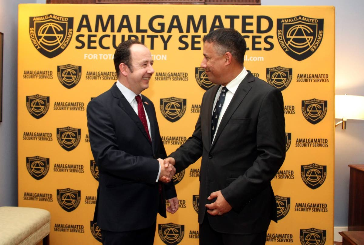 GOOD SHAKE: British High Commissioner to TT Tim Stew greets Commissioner of Police Gary Griffith at the commissioner's residence in Maraval on Wednesday night.