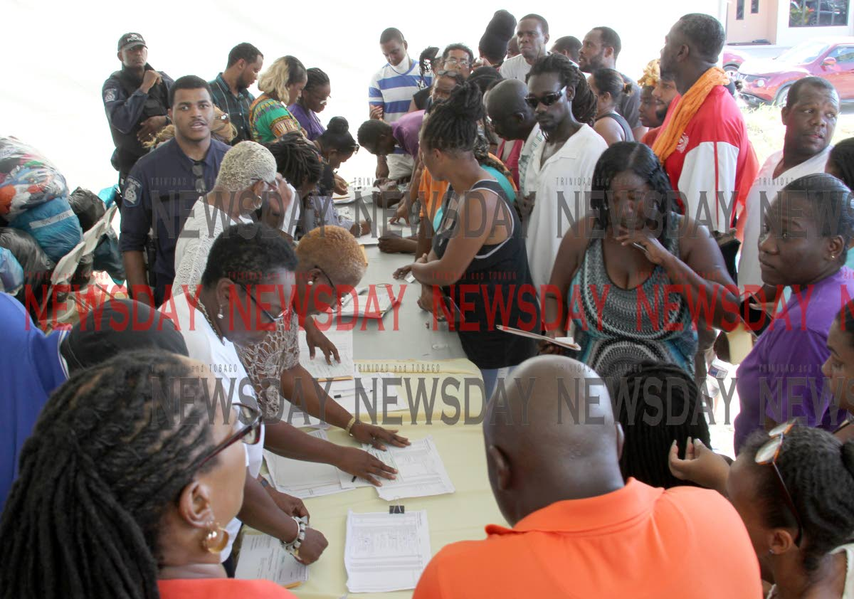 Residents wait to hear their names called to receive flood relief grants at Greenvale Park, La Horquetta in October. Grants were also issued in Sangre Grande and Mafeking, Mayaro. PHOTO BY ROGER JACOB