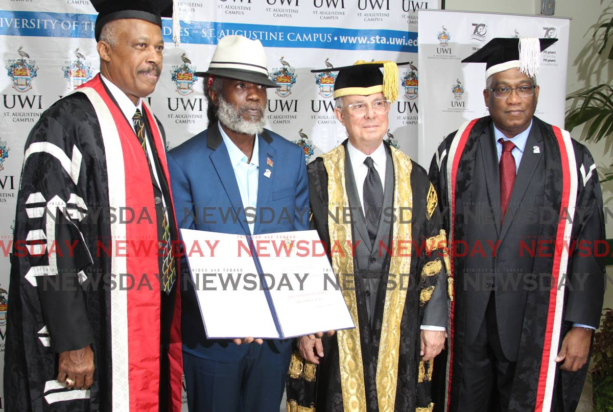 Sharlan Bailey holds the honorary doctor of letters degree he received on behalf of his father Winston