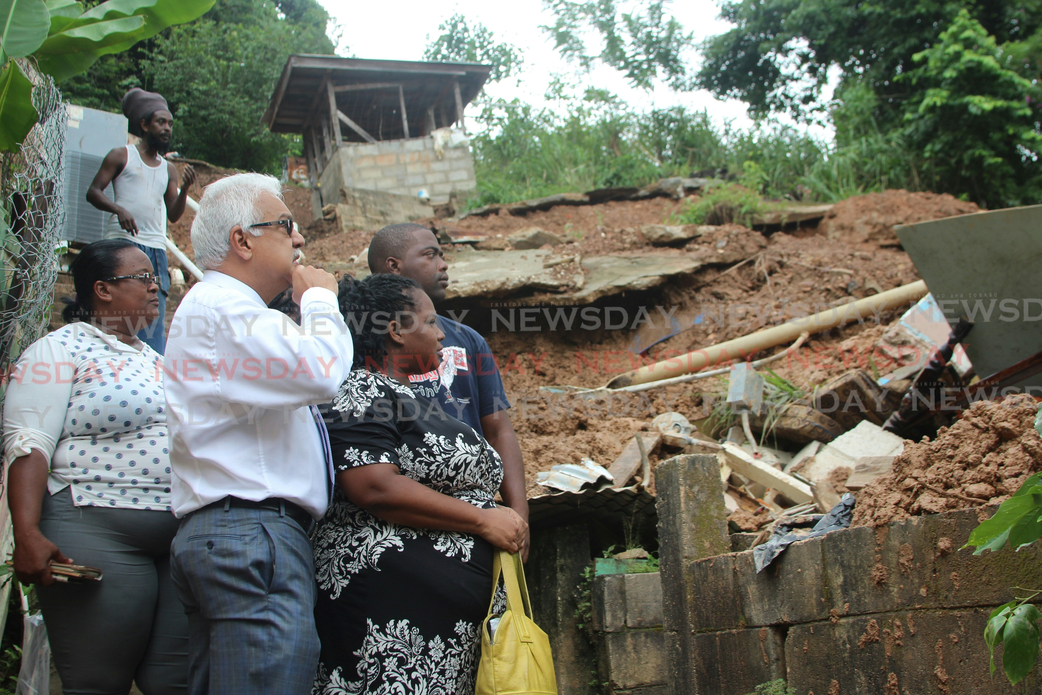 Minister of Health Terrence Deyalsingh visited the McKain family yesterday and their house fell during a landslide on Mt Lambert . Photo by Enrique Assoon