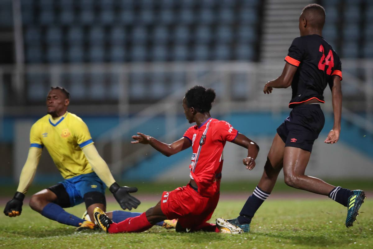 Morvant Caledonia's Sheldon Holder, centre, has his shot saved by North East Stars goalkeeper Glenroy Samuel, as defender Rakim Cabie looks on, in a TT Pro League match at the Ato Boldon Stadium, Couva. Photo by Allan V Crane/CA-images