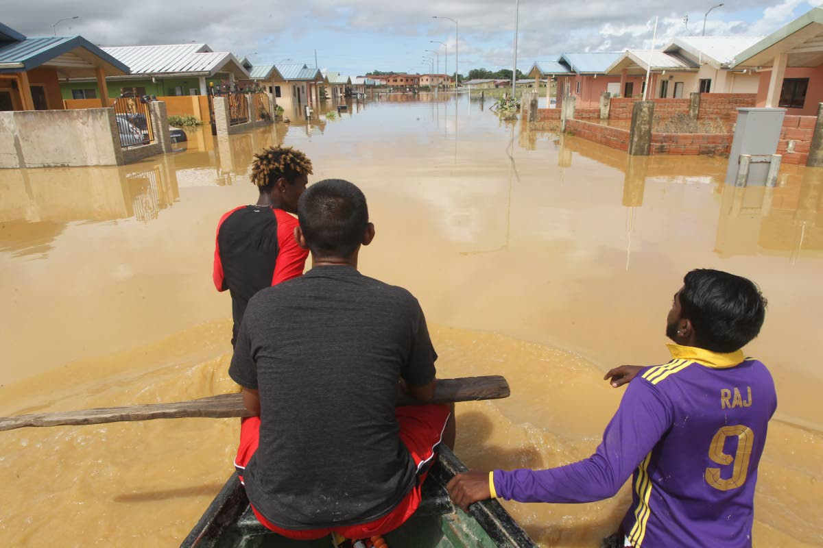 In this October 20 photo, Anil Boodhan and Avinash Deonarine and other residents check for persons needing rescuing following devastating floods in the HDC Greenvale housing development, La Horquetta. As the country recovers from the flooding, there are yet again calls for national building codes to be created and implemented. Photo by Lincoln Holder