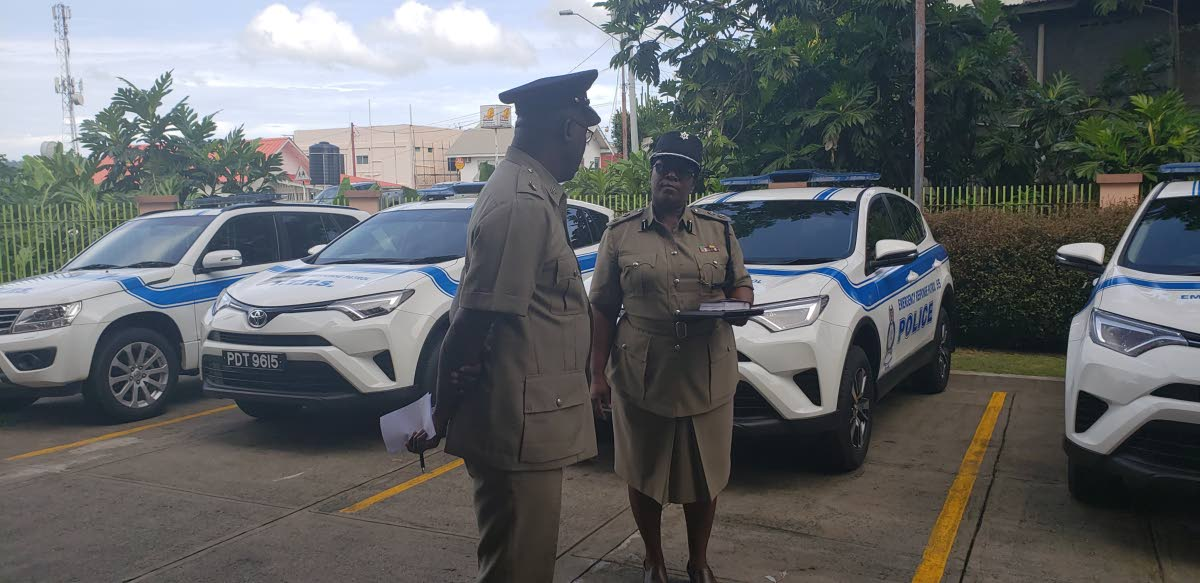 TALKING TOUGH: Ag Supt Tobago, Jeffrey George, chats with ACP Tobago, Sharon Blake-Clarke at the blessing of four new vehicles assigned to the new Emergency Response Unit at the Agricultural Development Bank Building in Scarborough on Friday.