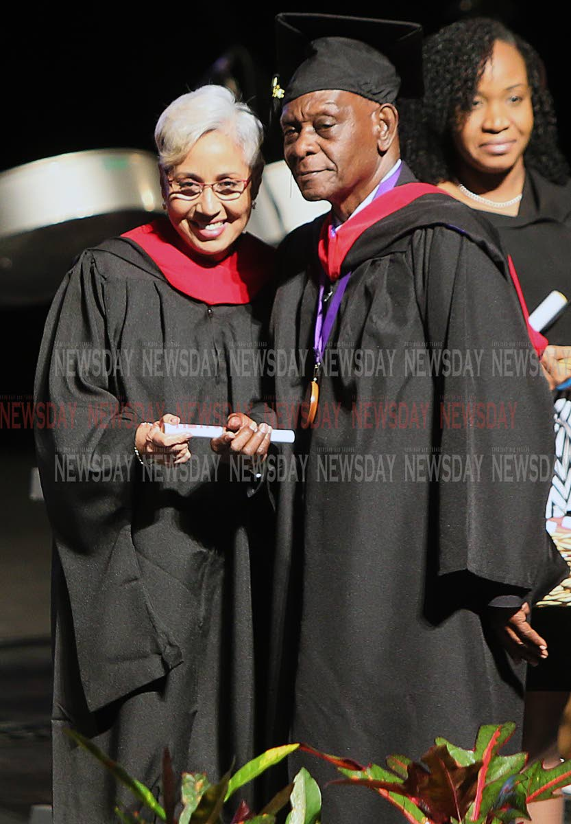 WELL DONE: After receiving his BA in Mass Communications on Sunday at the National Academy for the Performing Arts, Curtis Thomas, 84, poses with a fellow COSTAATT graduate.    PHOTO BY AZLAN MOHAMMED