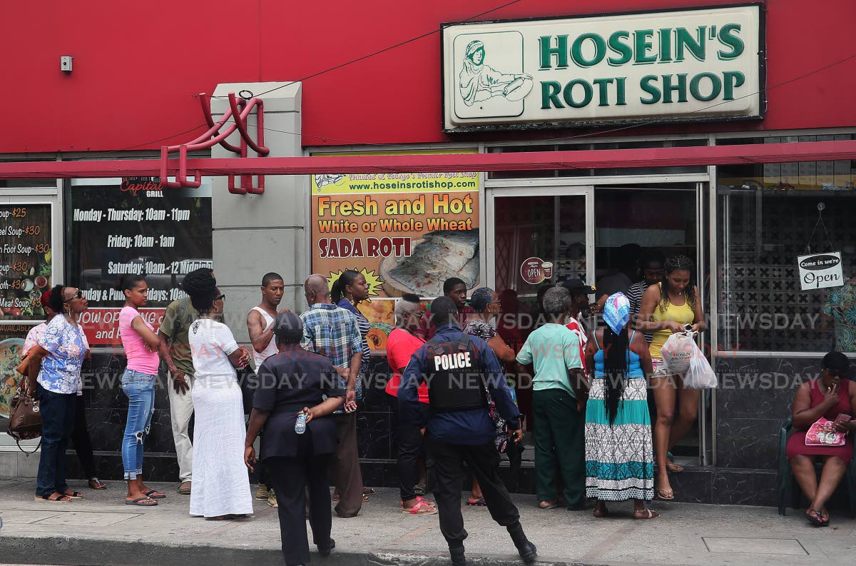 RUSH FOR ROTI: Police officers keep control of a large crowd in line to buy roti from Hosein's Roti Shop on Independence Square, Port of Spain, yesterday. Some lined up from as early at 5.30 am.