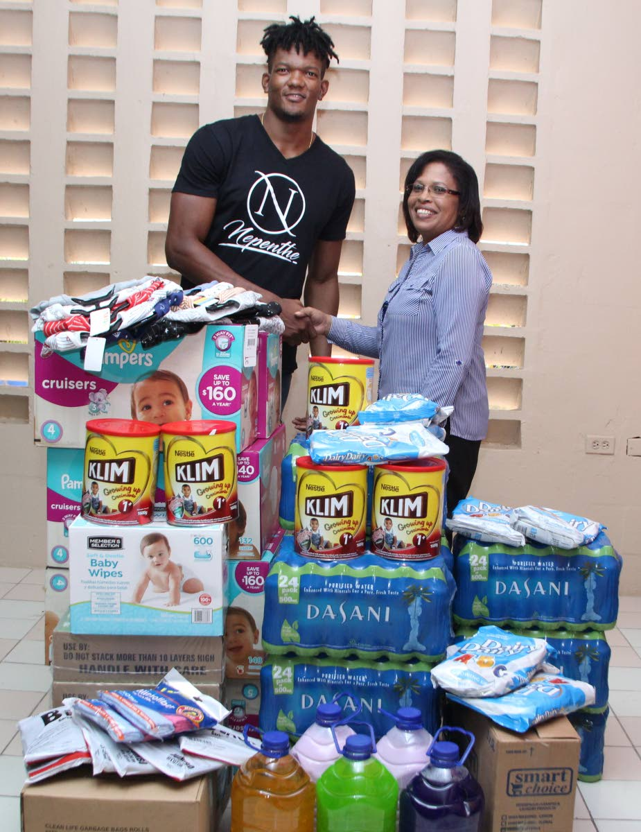 bmobile Brand Ambassador, Keshorn Walcott, presents relief items to the Bridge of Hope Children's Home Administrator. Proceeds from Walcott's Charity Event 'Nepenthe' were used to fund the donations.