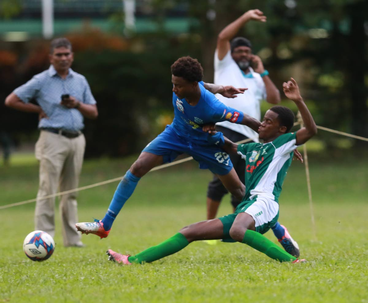 Naparima College's Seon Shippley (left) tries escape a challenge from  Trinity Moka's Adel Black-Haynes during the SSFL match at the Trinity grounds,yesterday. Photo by Nicholas Bhajan/CA-images