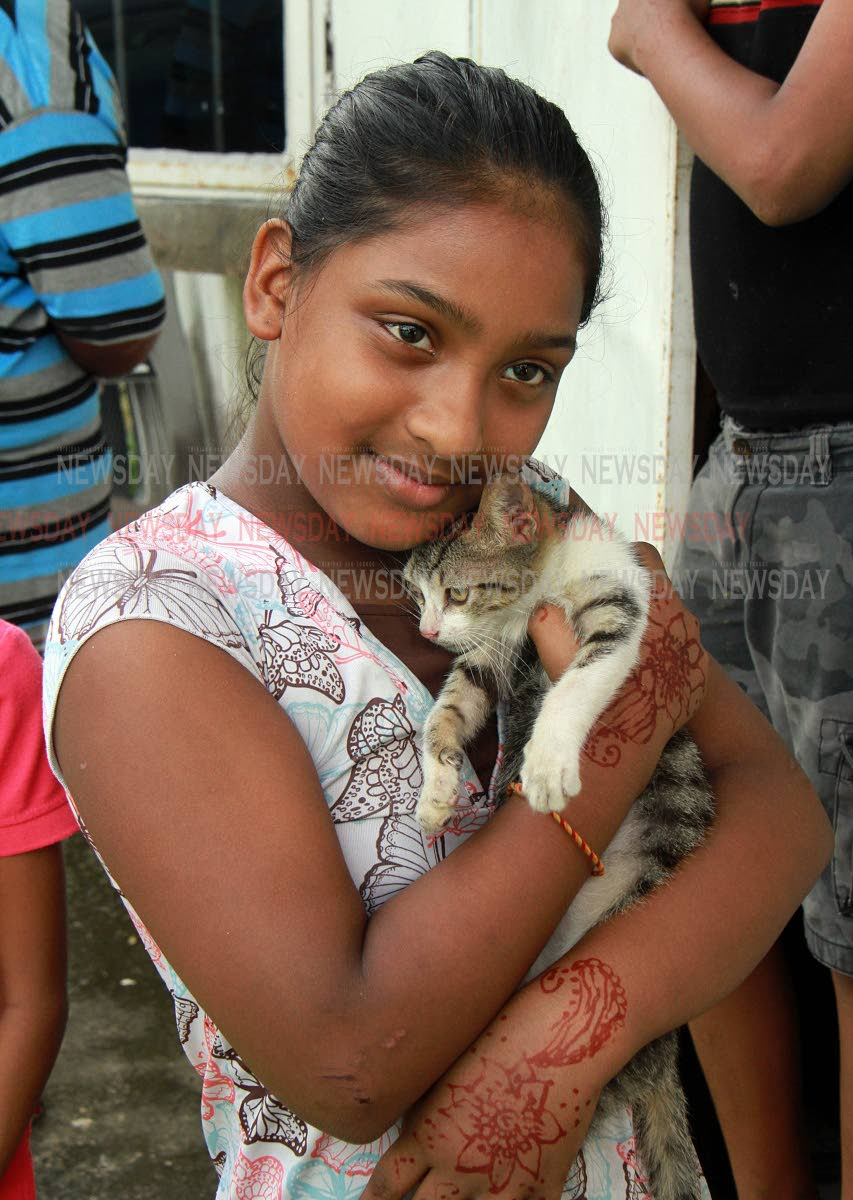 Michelle Rampersad, 10, hugs her pet cat after both of them are lucky to be alive when their family home was destroyed by fire on Divali Night at Baksh Settlement, Mc Bean, Couva. PHOTO BY ANIL RAMPERSAD.