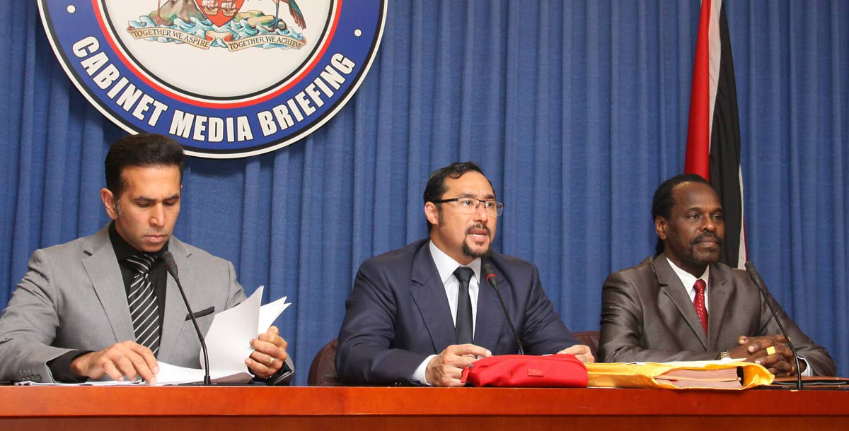 LEGAL BIRDS: National Security Minister Stuart Young, flanked by Attorney General Faris Al-Rawi and Minister in the Ministry of the AG Fitzgerald Hinds, addresses reporters at yesterday's post-Cabinet media briefing at the Diplomatic Centre, St Ann's.