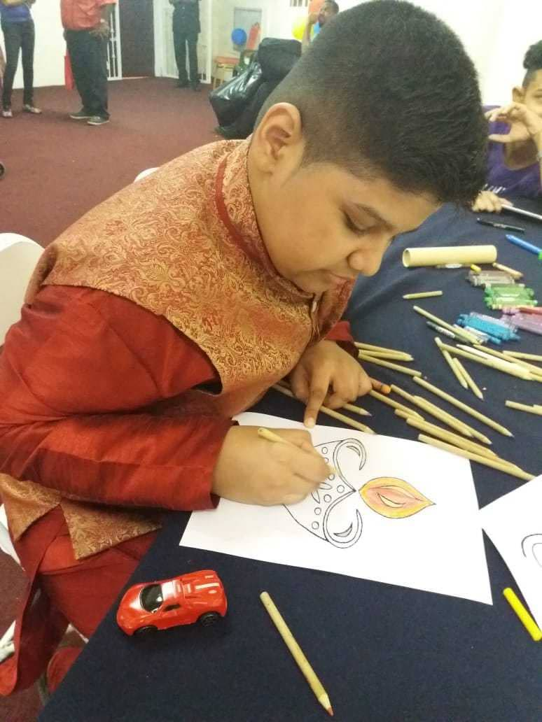 Akash is absorbed in a colouring activity at the Autism Outreach Booth at the Divali Nagar.