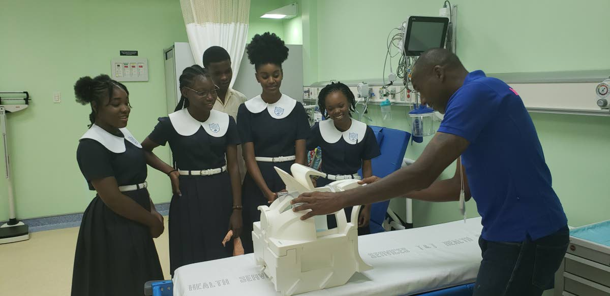 TRHA's MRI Technologist, Deon Edwards, conducts a demonstration with students of Harmon's SDA during last week's tour of the Scarborough General Hospital to commemorate World Radiography Day 2018.