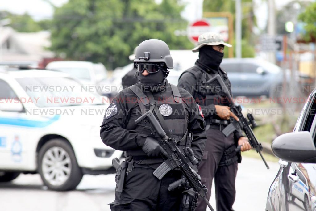 Members of the National Security special operations group stand watch outside the Chaguanas Magistrate Court as accused Jerome Oliverre attends court to answer charges of drug trafficking, arms and ammunition.  Photo by Lincoln Holder
