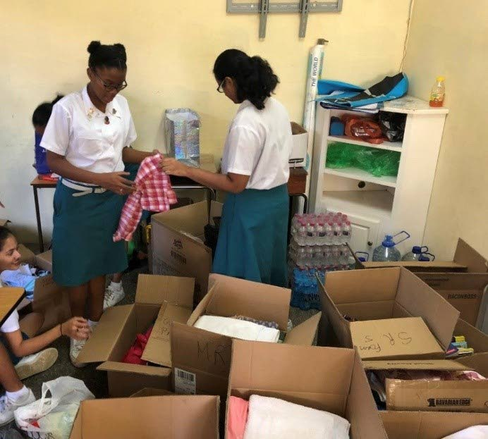 Some of the interactors working tirelessly during the Flood Relief Drive where packages were donated to persons affected by flood as well as Our Lady of Fatima RC Church.