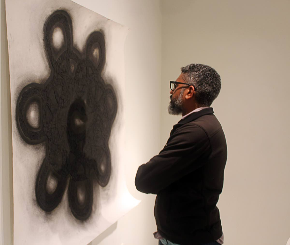Nikolai Noel ponders the impact of one of his pieces for his exhibition The Last Place on Earth/The Edge of All Things at Medulla Art Gallery, Woodbrook. PHOTO BY ENRIQUE ASSOON