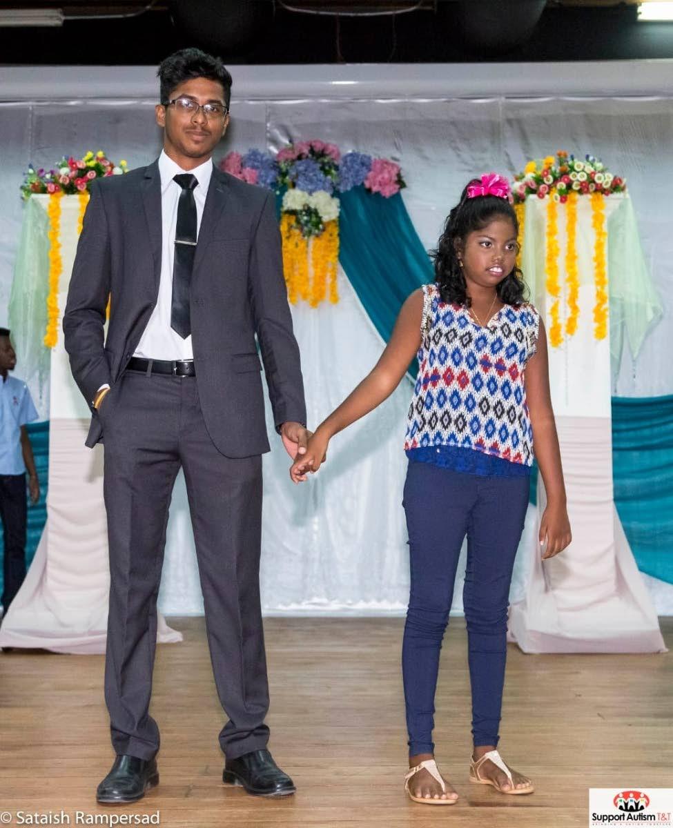 Rajeev Ramlakhan escorts little Sidney Mahabir at  Support Autism TT's recent Autism fashion show.