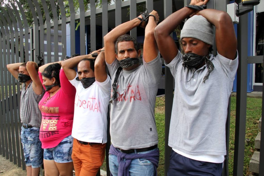 LET US STAY: Cuban asylum seekers symbolically sealed their  mouths and tied their hands to the fence outside the United Nations' office in Port of Spain yesterday, after 78 of their fellowmen  were arrested and charged with obstruction the passageway  at Chancery Lane.  PHOTO BY SUREASH CHOLAI