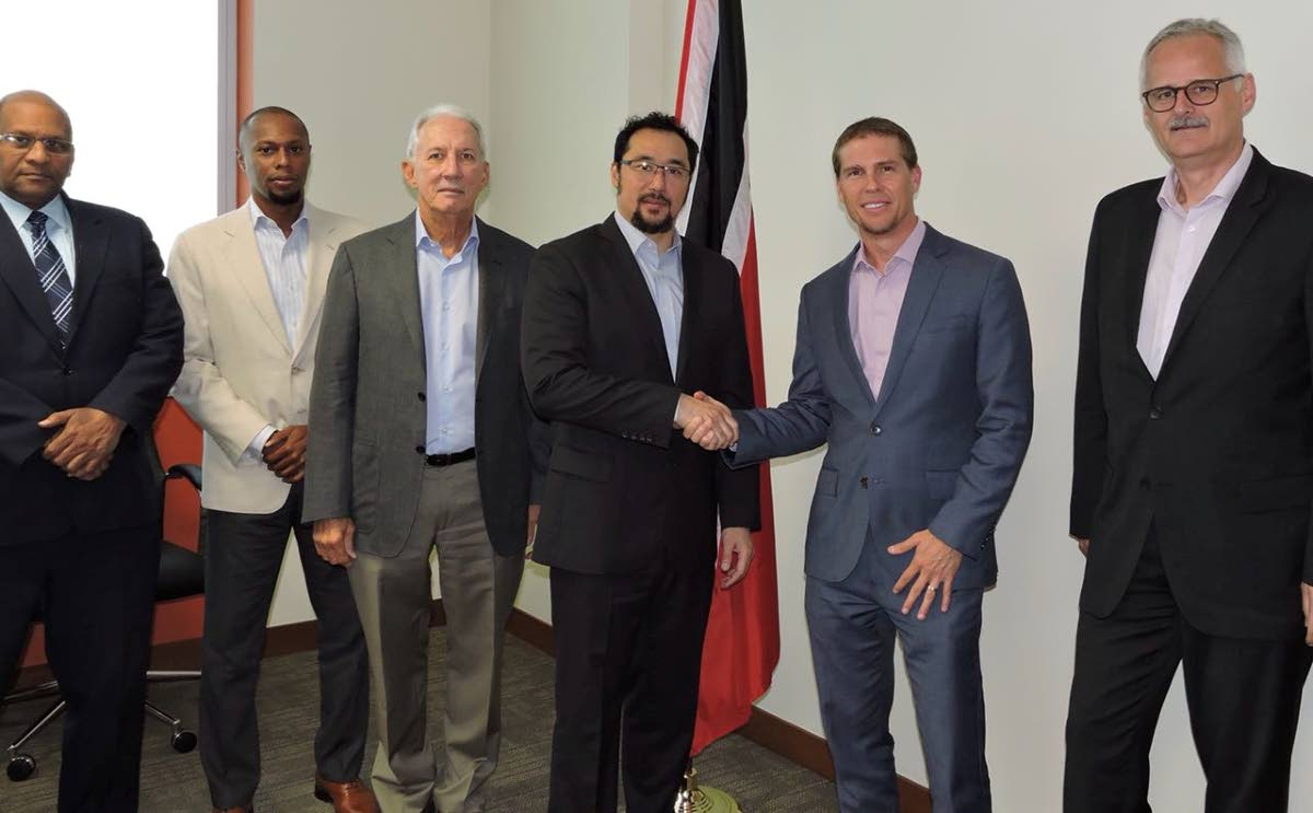 Communications Minister Stuart Young, fourth from left, shakes hands with Sandals Resorts InternationalI deputy chairman Adam Stewart at a meeting to discuss the Sandals Tobago project.