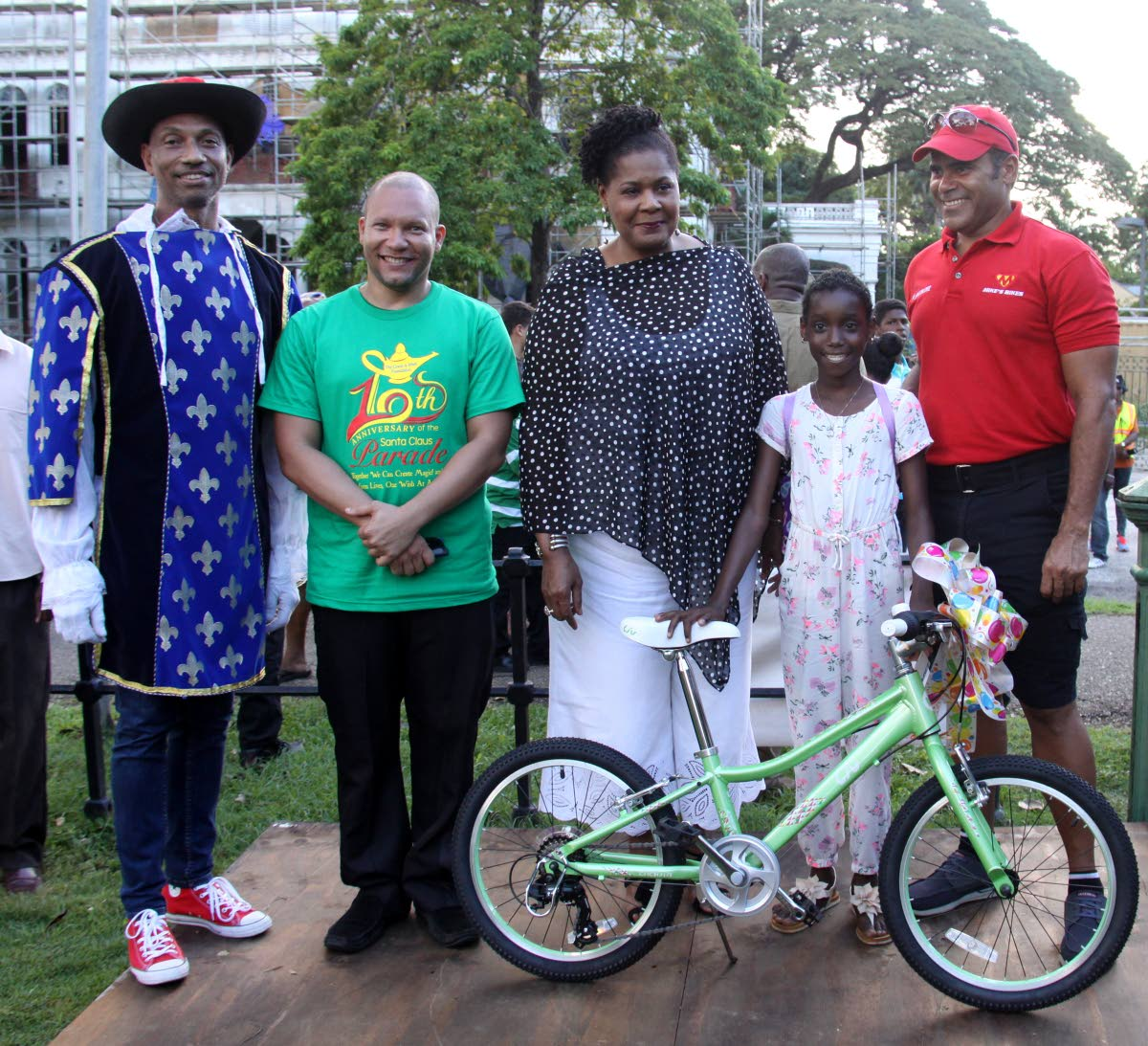 President Paula-Mae Weekes, centre, with Shirmia Espinoza who received  a bicycle as a Christmas gift at the Grant-A-Wish Foundation, tenth Santa Claus Parade, Queen's Park Savannah on Sunday afternoon. From left is Dr Curt Bodkyn, Nicholas Gordon and former national cyclist, Michael Phillips.