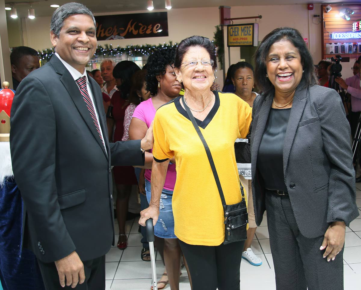First customer: Dave Paladee, Pennywise Cosmetics managing director and CEO, and Trade Minister Paula Gopee-Scoon welcome Maureen Christopher (centre) the first customer at the newly opened Pennywise Cosmetics store in Long Circular Mall, St James. Photo by Azlan Mohammed
