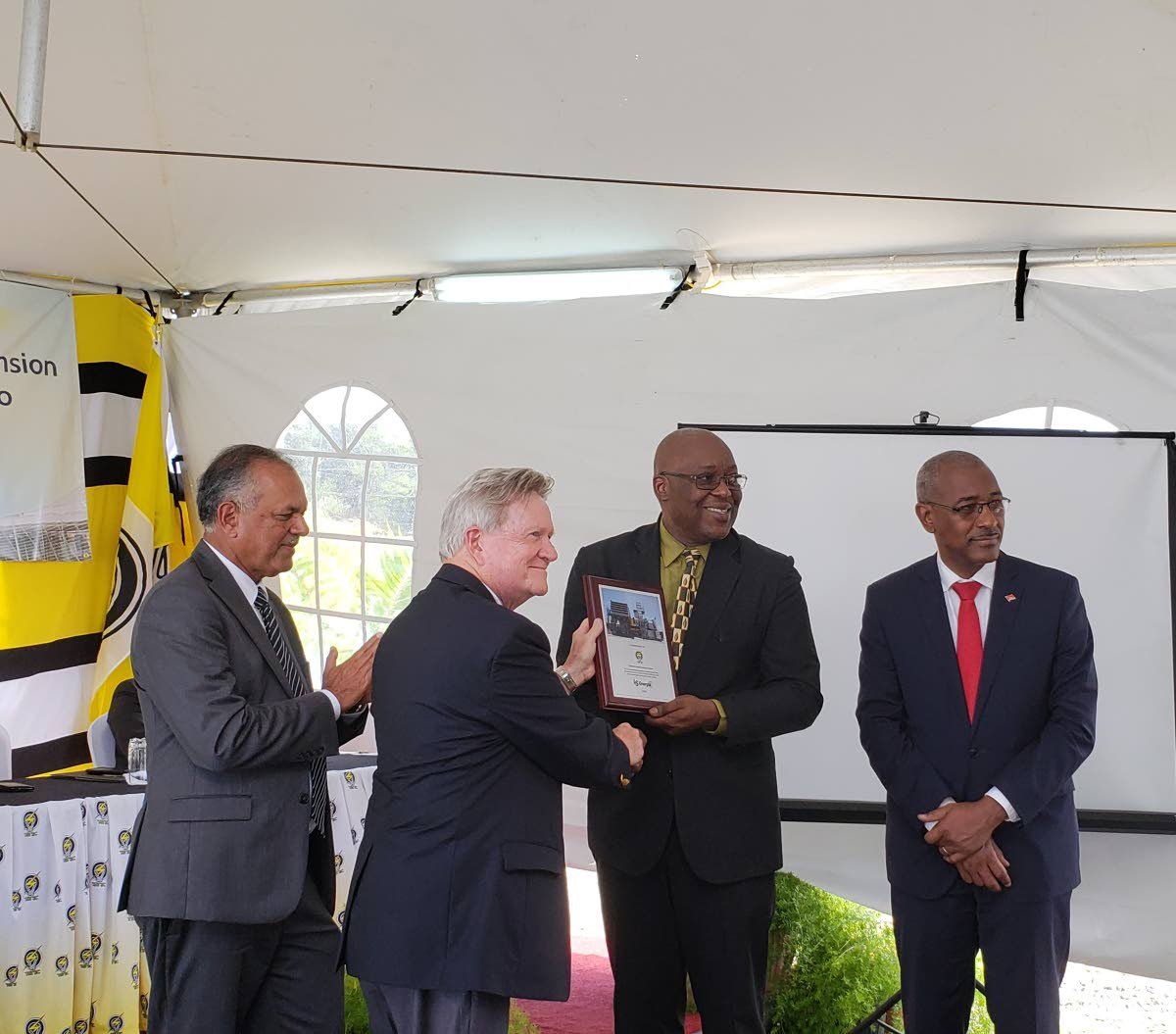 THA Chief Secretary Kelvin Charles, second from right, is presented with a plaque by a representative from LS Energia Inc, project consultants for the expansion of capacity for T&TEC's Cove Power Plant at the commissioning on Monday. Looking at right is Minister of Public Utilities Robert Le Hunte and T&TEC's Chairman Keith Sirju.↔PHOTOS BY Kinnesha George-Harry
