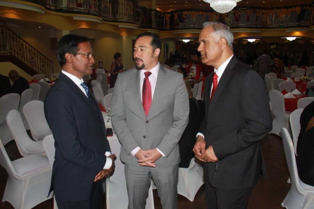 National Secuity Minister chats  with present and  past president of the  Chaguanas Chamber of Industry and  Commerce at a Christmas Dinner at  Passage to Asia