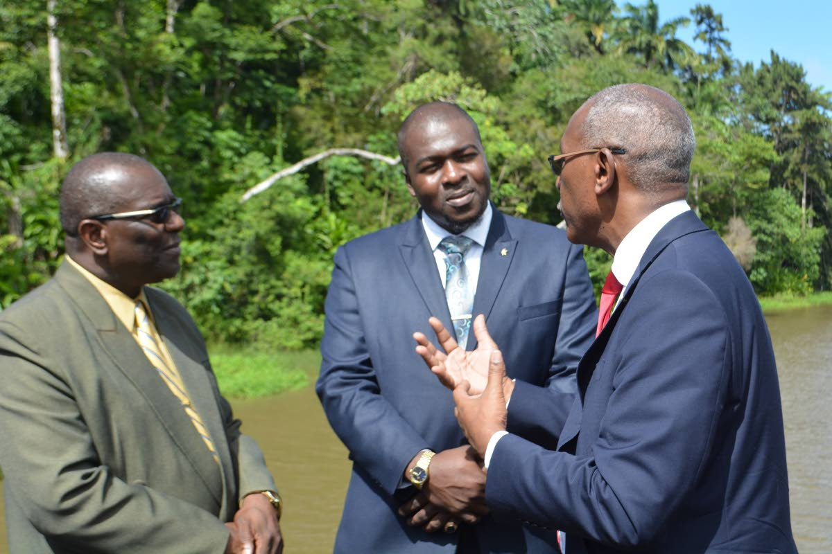 Public Utilities Secretary Clarence Jacob, centre, listens as Public Utilities Minister Robert Le Hunte, right, makes a point during a visit to the Hillsborough dam last week Monday. At left is Water and Sewerage Authority chairman, Ellis Burris.