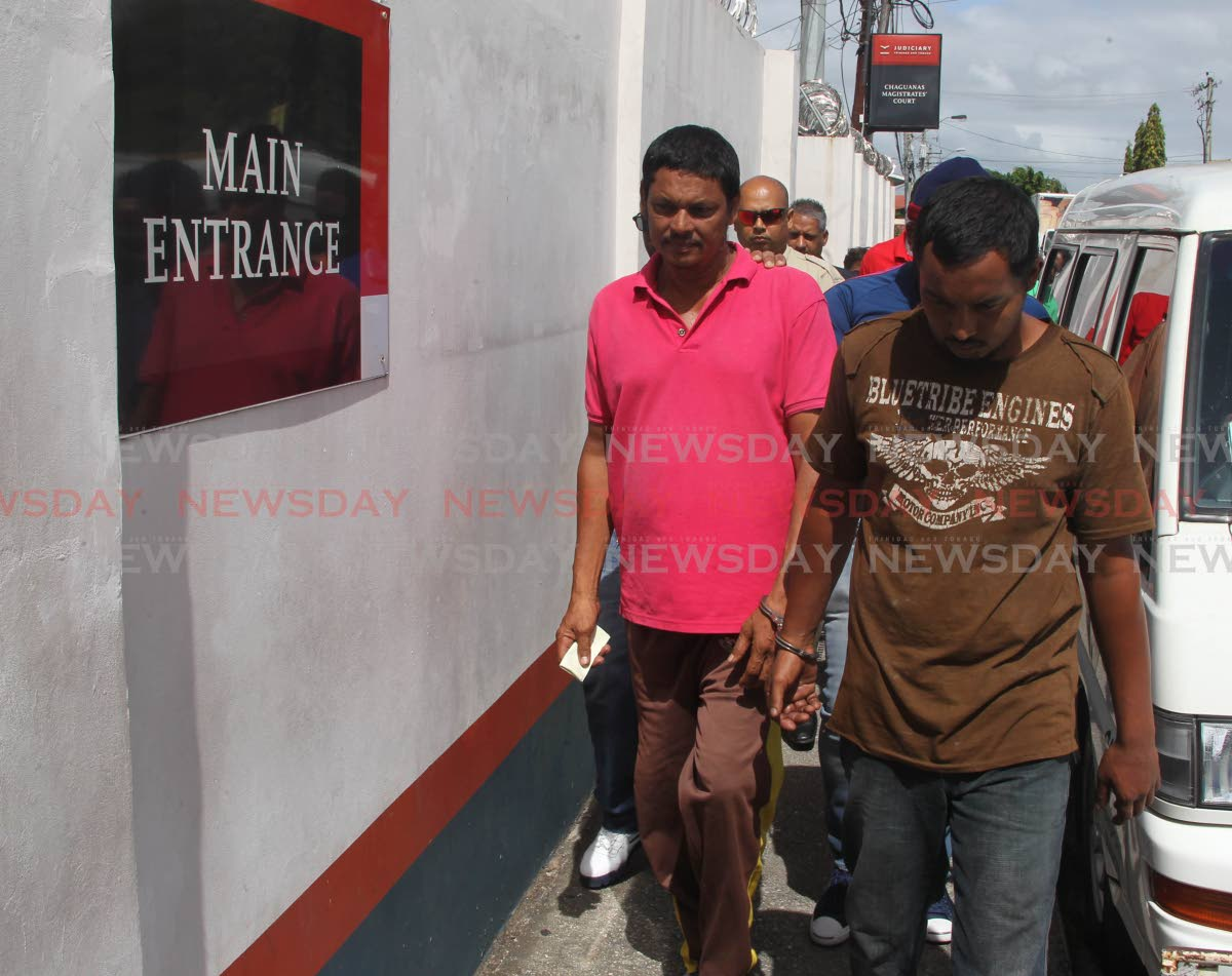 Indaraj Mahabir, 50 (left) and son, Kimraj Mahabir is escorted to the Chaguanas magistrate's court  after being charged with five counts of having in their possession carcasses of the scarlet ibis and hunting Iguanas on state lands. Photo by Lincoln Holder