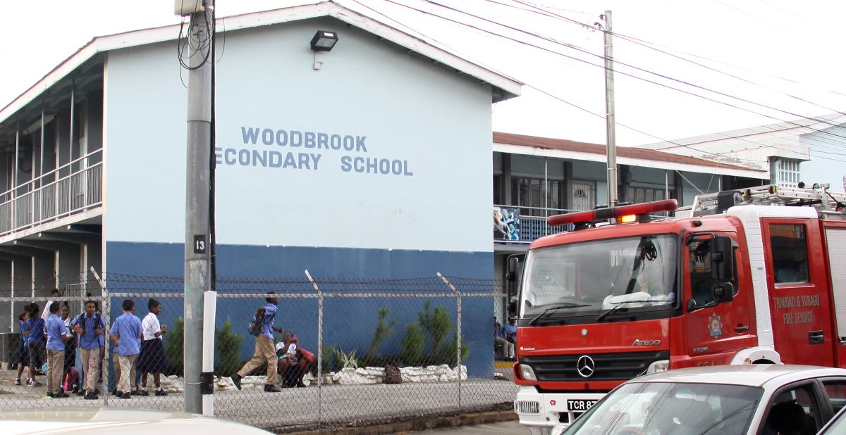 A fire truck parked outside the Woodbrook Secondary School yesterday after a mini-tornado damaged part of the school's roof.