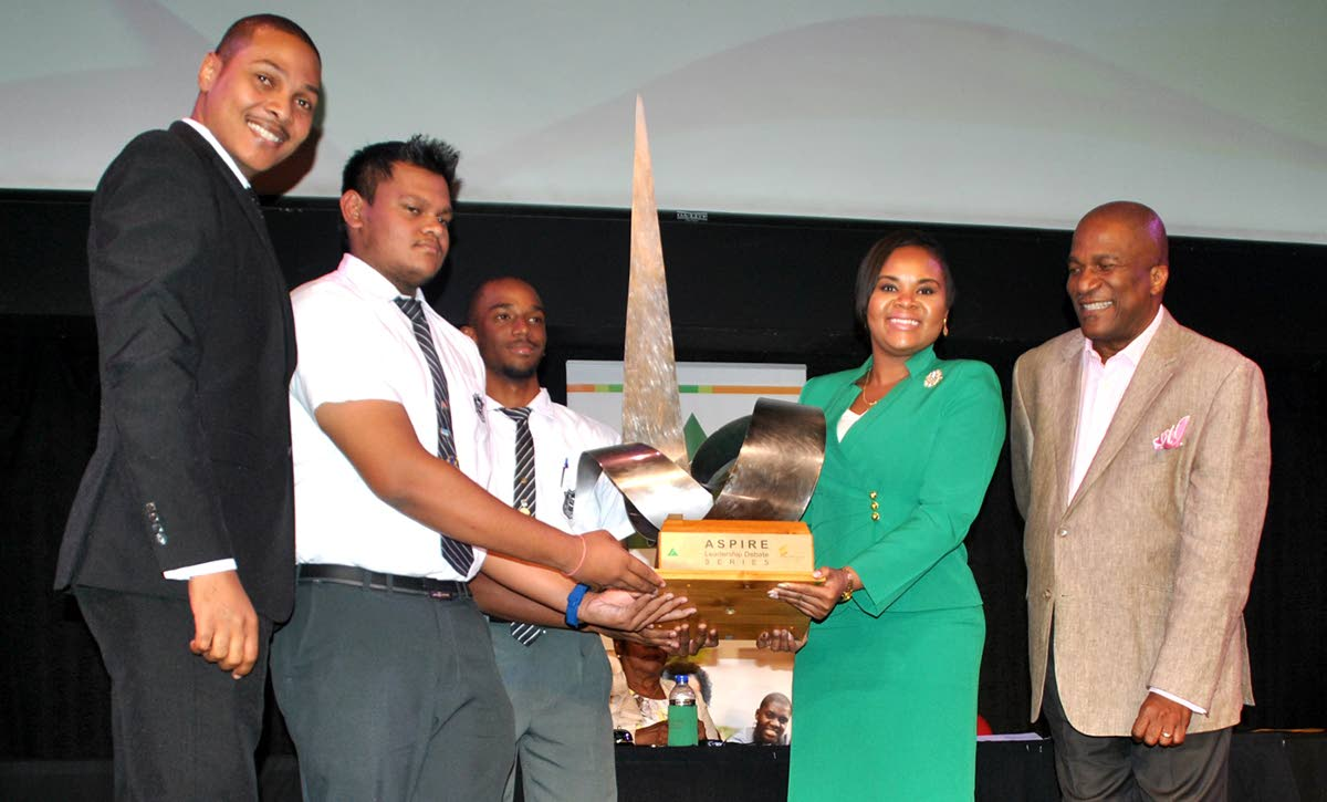 Minister of Sport and Youth Affairs, Shamfa Cudjoe, presents the JA Leadership Debate Series championship challenge trophy to Vashisht Ramoutar (second from left), lead debater for Naparima Boys College Team A and his fellow student, Joel Beckles. At left is  Nigel De Freitas, vice president of the Senate, and J Errol Lewis, JA executive director.