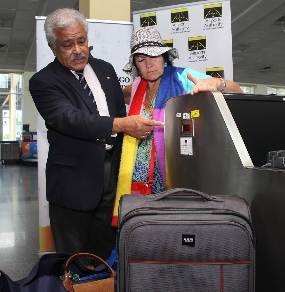 Lawford Dupres, chairman of the TT Bureau of Standards verifies a baggage scale at the Piarco International Airport, yesterday, closely watched by London-bound passenger, Lizzie Gibson. Photo by Angelo Marcelle