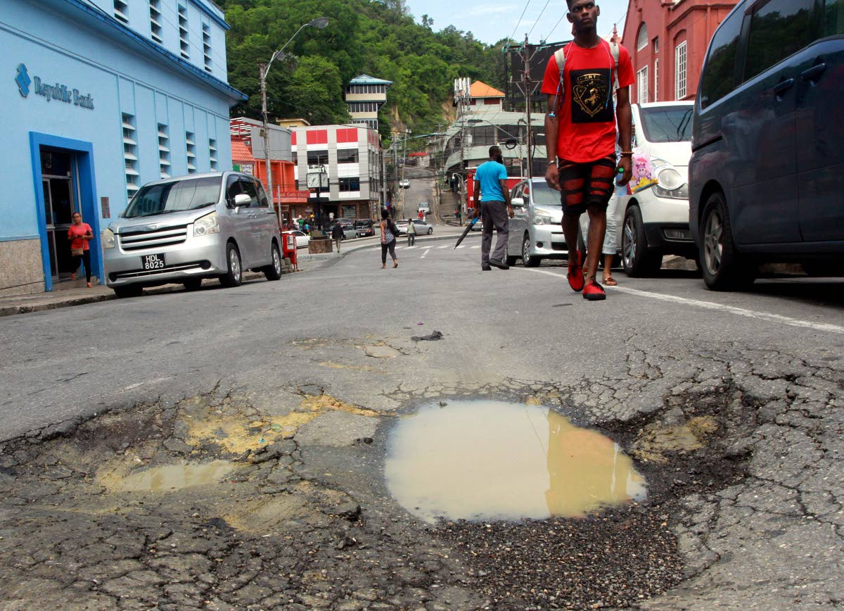 A pedestrian walks past a huge pothole near Library Corner, San Fernando in this July 3, 2018 file photo. PHOTO BY ANIL RAMPERSAD.