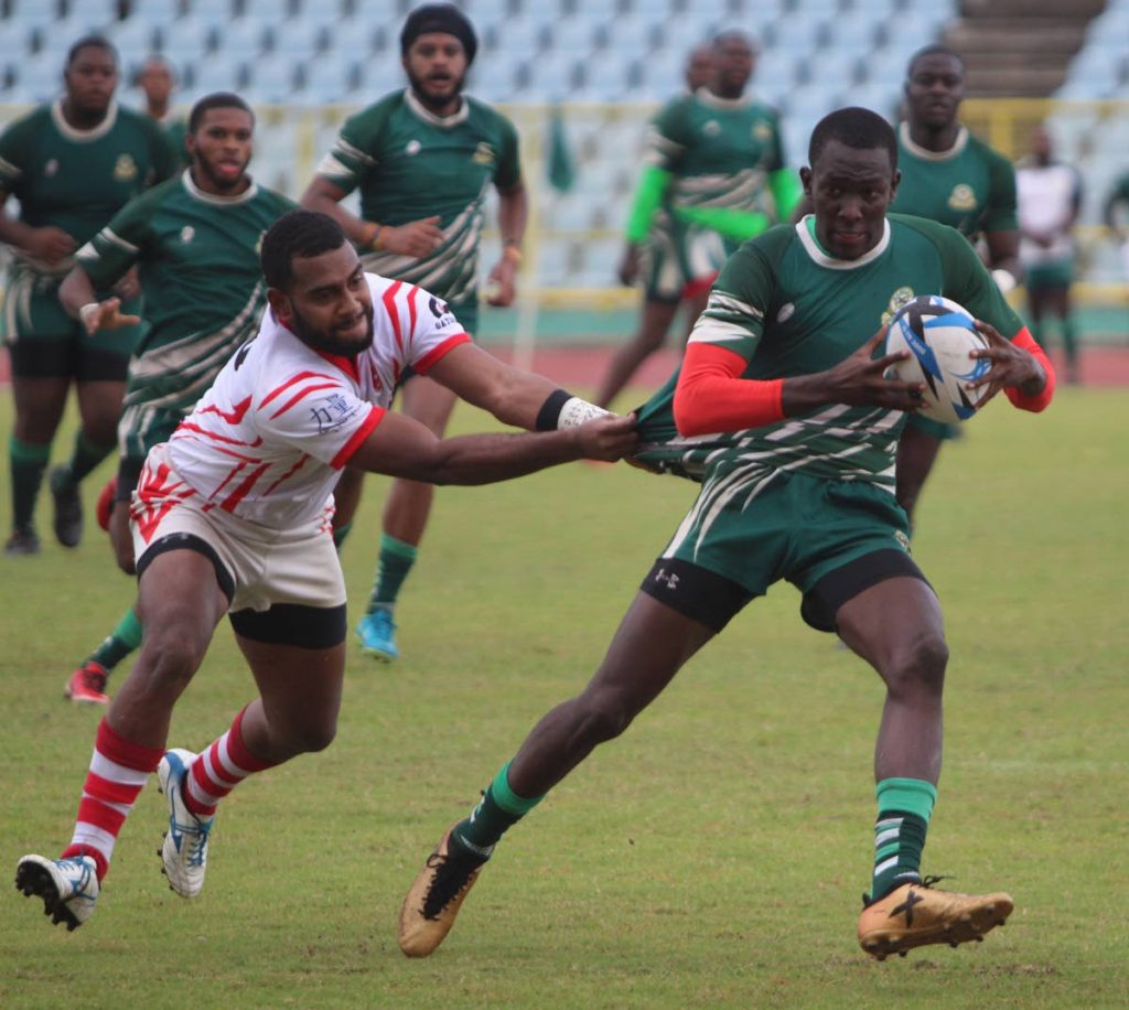 FLASHBACK: Harvard's Joseph Quashie, right, fends off a Caribs player in a TT Rugby Football Union championship clash at the Hasely Crawford Stadium, Mucurapo, earlier this year.