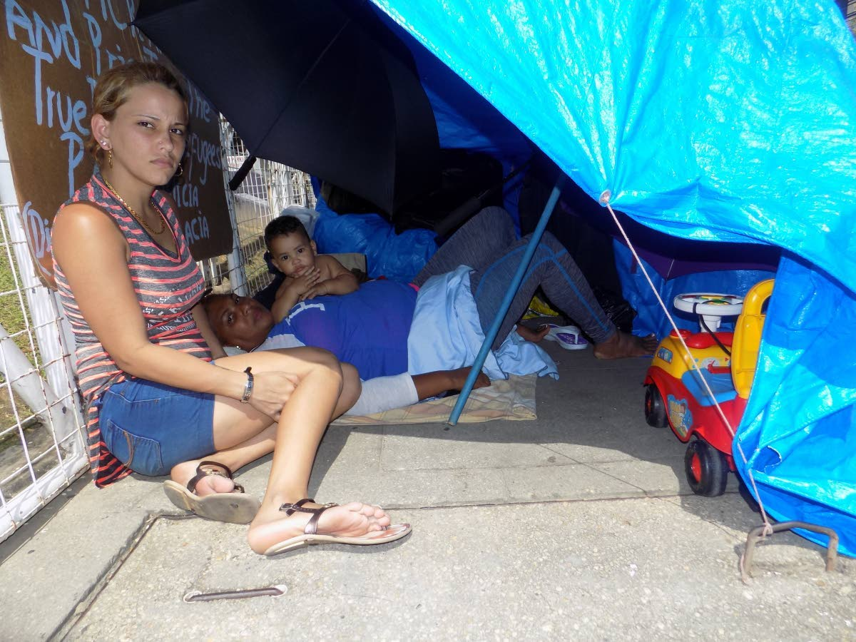 Cuban asylun seekers Lisa Perez, her mother Sandra Rodriguez and infant son Liusnel Perez take shelter under a tarpaulin, tied to the gate of the United Nation's building in Chancery Lane, Port of Spain in  December 2017. File photo