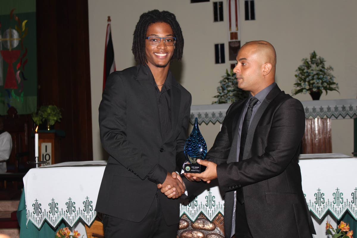 Alderman Johannes Deonarine, awards Mikhaili Toney in recognition of his outstanding achievement in education.